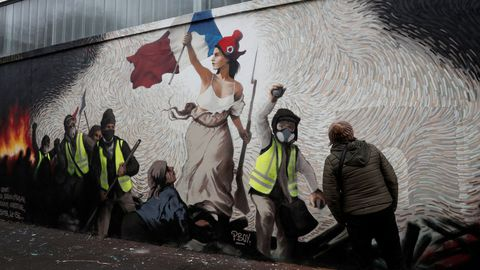 a woman inspects a new mural by the artist pascal boyart aka pboy to pay homage to the yellow vests movement and containing 0 26btc 1000 on a wall in